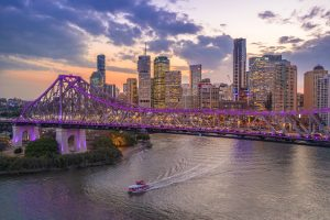 The Story Bridge lit up in Purple lights as the sun sets